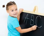 Cute little girl is showing letter E on the alphabet in preschool