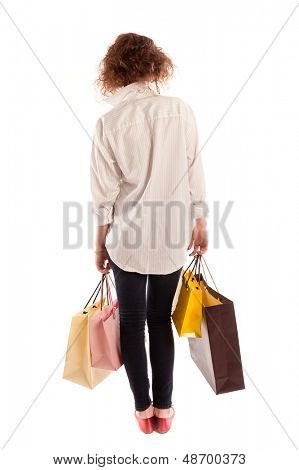 Young woman walking away with shopping bags, isolated on white background