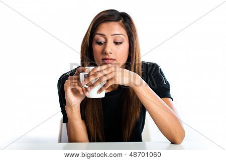 Attractive young asian indian woman looking down at her hot drink