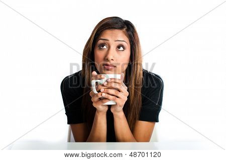 Attractive young asian indian woman thinking and enjoying a drink