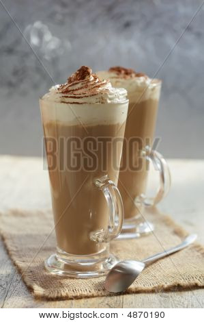 Coffee Latte Macchiato With Cream In Glasses On Window Background