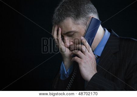 Closeup of a worried businessman using landline phone against black background