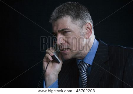 Closeup of a worried businessman using landline phone against black background
