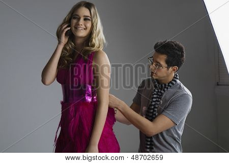 Male designer adjusting dress on a fashion model while she's on call in studio