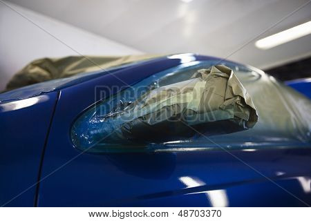 Closeup of damaged headlight of a blue car