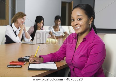 Portrait of a confident businesswoman with multiethnic colleagues in conference room