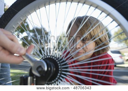 Closeup of a boy watching cropped father fix his bicycle tyre