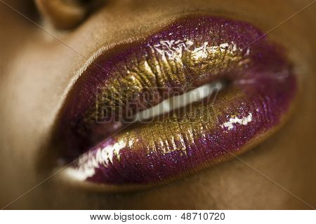 Detail shot of an African American woman's purple and golden lips