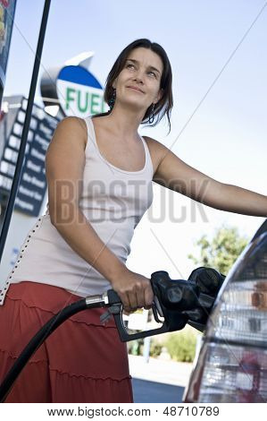 Smiling woman refueling cropped car at the natural gas station