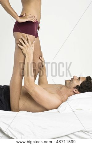 Lowsection of a woman in underwear with man in bedroom