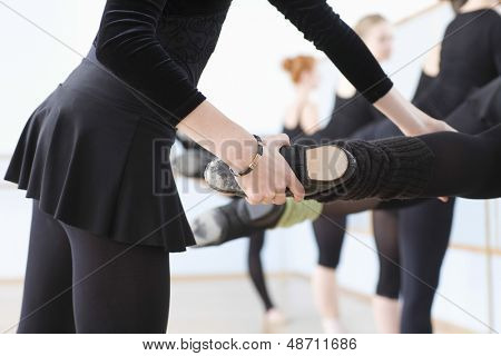 Midsection of ballet teacher adjusting foot positions of ballerinas at the barre