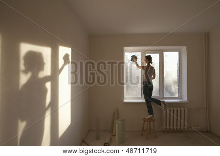 Full length rear view of young woman cleaning window in new apartment