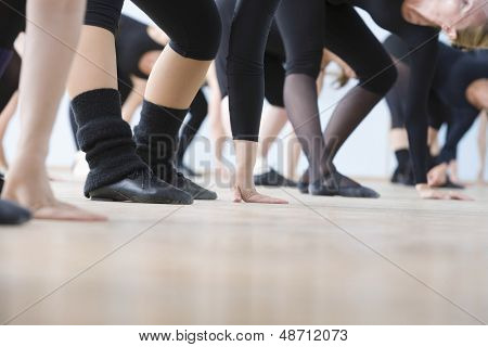 Low section of ballet dancers practicing in rehearsal room