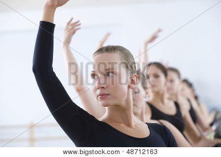 Beautiful young woman with classmates practicing at the barre in ballet rehearsal room