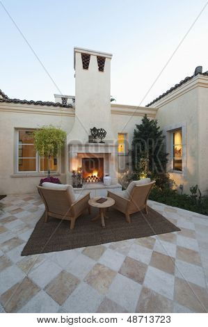 Outdoor room at dusk with fireplace and furniture