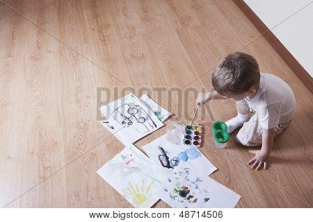 Vista elevada de joven, pintar con acuarelas y pincel en piso laminado