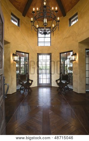Wood floored foyer with candelabra hanging from high ceiling