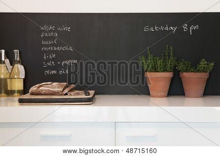 Pan de tajadera con compras lista escrita en la pizarra en la cocina