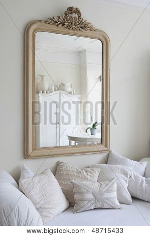 Framed mirror above daybed with cushions