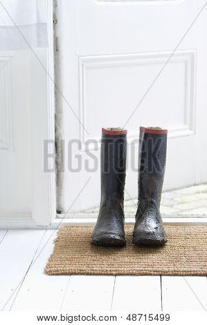 Muddy wellington boots on door mat