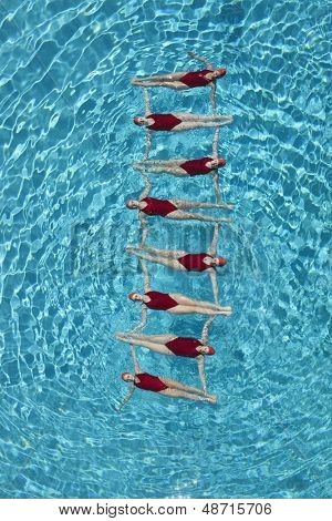 Group of synchronised swimmers forming a ladder in pool
