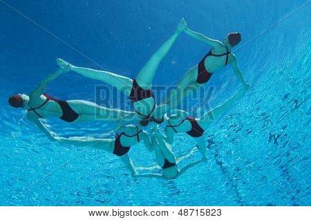 Underwater view of synchronized swimmers forming a star shape in pool