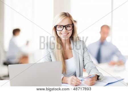concepto del negocio - sonriente con ordenador portátil, documentos y pluma en oficina