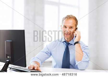 business and technology concept - smiling businessman with smartphone in office