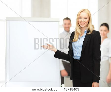 bussiness, meeting and education - businesswoman with flipchart in office