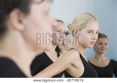 Serious young female ballet dancer with classmates in rehearsal room
