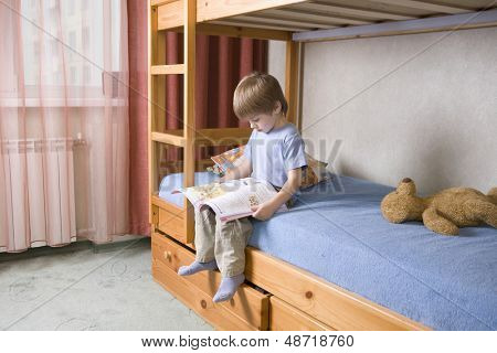 Full length of young boy reading book on bunk bed