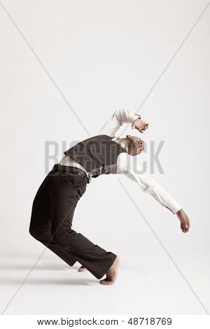 Full length of young man dancing jazz over white background