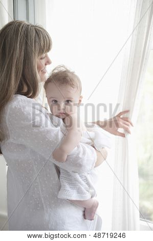 Smiling mother holding baby boy while looking through window