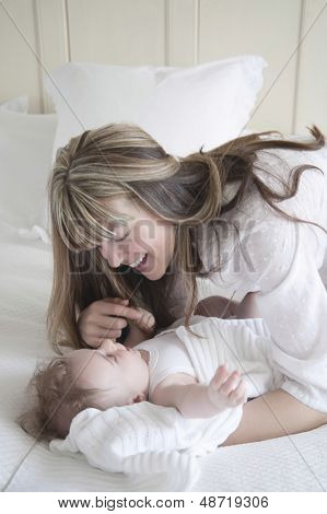 Smiling mother looking at baby boy in bedroom