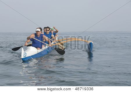 Multiethnic outrigger canoeing team on water