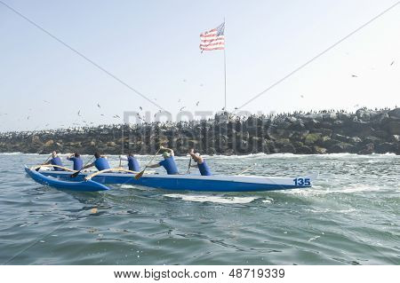Side view of multiethnic outrigger canoeing team heading to race stage