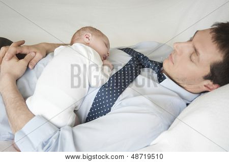 Two week newborn baby sleeping with father in bed