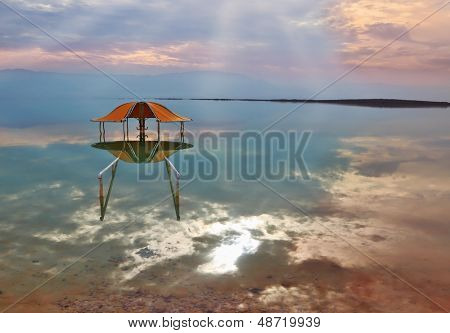 Fantastically beautiful optical effects at the Dead Sea. The picturesque arbor for bathers is reflected in a smooth sea surface
