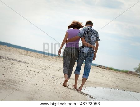 Man And Woman Are Walking Near The Sea