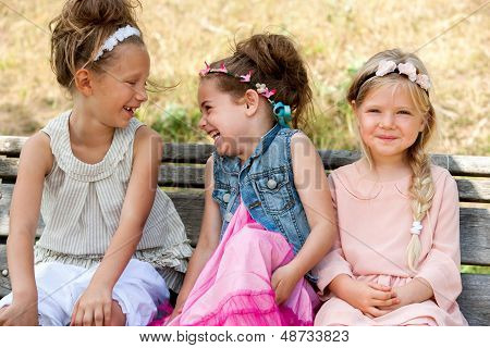 Laughing Kids Sitting On Wooden Bench.
