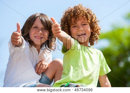 Two Cute Boys Doing Thumbs Up Outdoors.