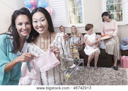 Porträt einer glücklichen Frau mit Freund Angeberei Geschenk zur Babyparty