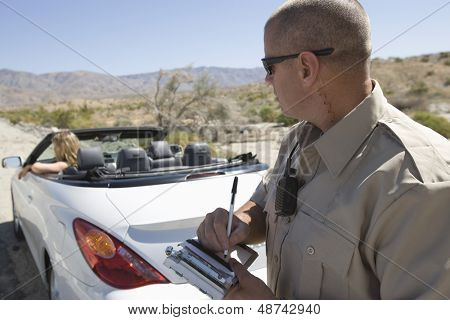 Closeup of a police officer writing traffic ticket to woman sitting in car