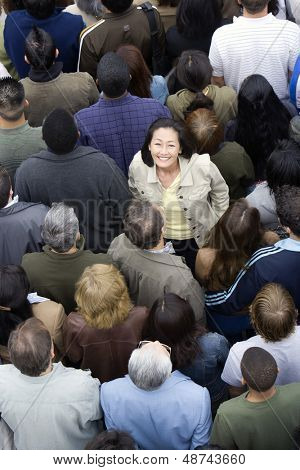 Portrait of happy Asian Chinese woman standing amidst around the people