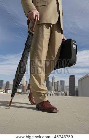 Sección baja de un empresario caminando con paraguas y maletín contra edificios urbanos