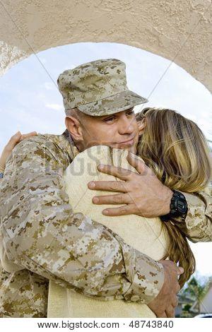Jovem soldado abraçando sua mulher ao ar livre