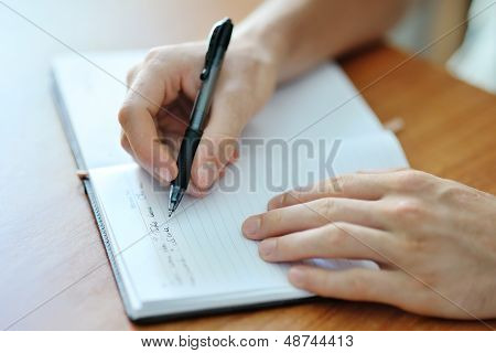 Male Hand Writing On A Notebook