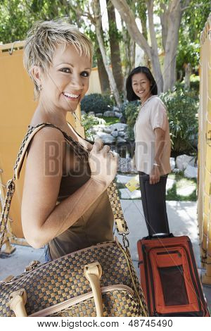 Two happy multiethnic female holidaymakers with luggage