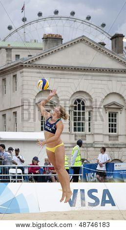12/08/2011 LONDON, ENGLAND, Lucy Boulton (GBR) serves with the Millenium wheel in the background during the FIVB International Beach Volleyball tournament, at Horse Guards Parade, Westminster, London.