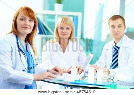 Portrait of female clinician looking at camera with her colleagues on background
